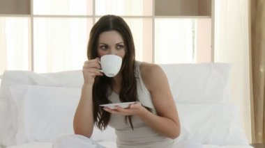 Beautiful woman drinking a cup of coffee in bed — Stock Video