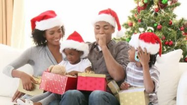 Footage in high definition of Afro-American family opening Christmas gifts on the sofa — Stock Video