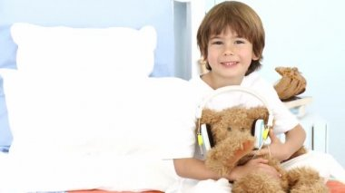 Little boy and teddy bear listening to music on bed — Stock Video