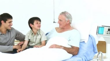 Man and kid visiting a senior man recovering in hospital — Stock Video