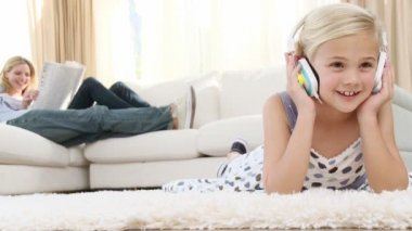 Little girl listening to the music on the floor of the living-room — Vídeo de Stock