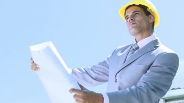 Engineer working outdoors with plans and a hard hat on — Stock Video