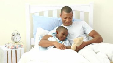 Afro-American father and sick son playing doctors in bed — Stock Video