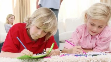 Children painting in living-room and parents on sofa — Stock Video #22642211