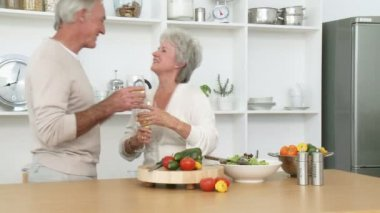 Footage in high definition of smiling senior couple preparing a salad in the kitchen and drinking wine — Vídeo de stock