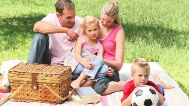 Parents and children sitting in a park before having a picnic. Footage in high definition — Vídeo de stock