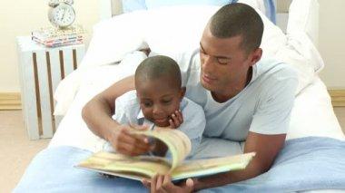 美国黑人小男孩与他的父亲躺在床上读一本书 — 图库视频影像