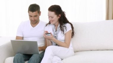 年轻的夫妇在家里使用的便携式计算机 — 图库视频影像