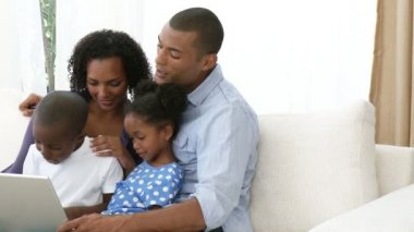 Panorama of Afro-American family using a laptop on the sofa — Stock Video