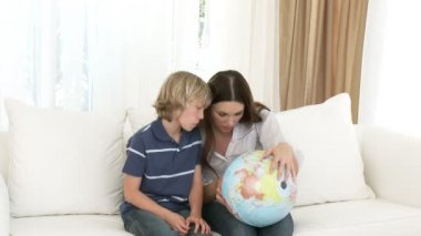 Mother and son examining a terrestrial globe — Stock Video