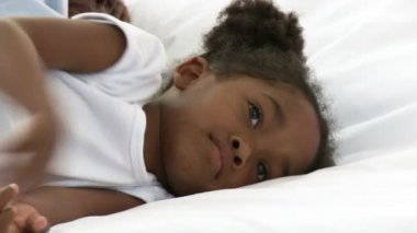 Afro-American little girl lying in her parent's bed — Stock Video