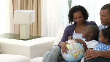 Afro-American family examining a terrestrial globe — Stock Video
