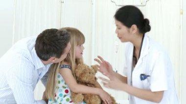 Doctora hablando con una niña y su padre — Vídeo de stock