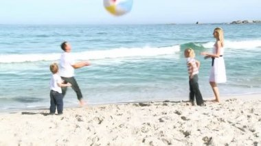 Family playing with a ball on the beach — Stock Video