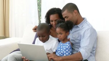 Afro-American family using a laptop on the sofa — Stock Video