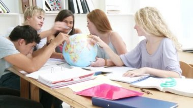 Teenagers in a library working with a terrestrial globe — Stock Video
