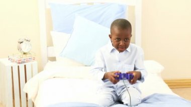 Afro-American little kid playing video games in his bedroom — Stock Video
