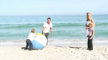 Family playing with a ball on the sand — Stock Video