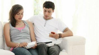 Coppia di adolescenti mangiare hamburger e parlando sul divano — Video Stock