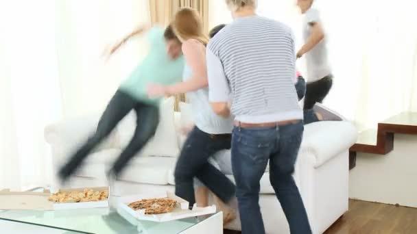 Adolescentes corren para comer pizza en la sala de estar — Vídeo de stock