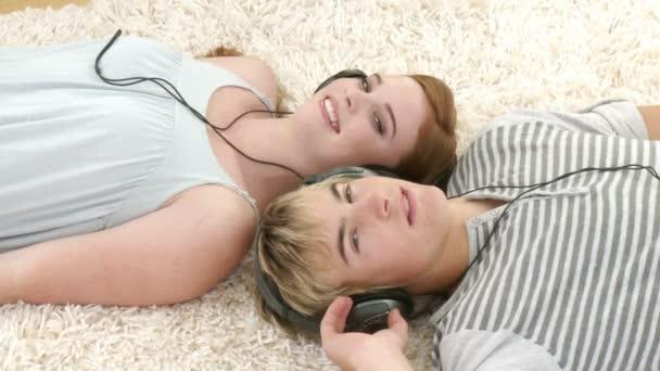 Pareja adolescente escuchando música mientras se relaja — Vídeo de stock