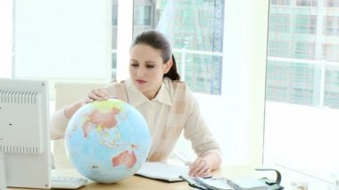 Elegant businesswoman looking at a terrestrial globe — Stock Video