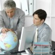 Fortunate business team looking at a terrestrial globe — Stock Video #22702365