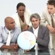 Multi-cultural business team looking at a terrestrial globe — Stock Video