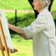 Stock Video: Old wompainting white canvas in Park