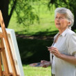 Stock Video: Old female painting canvas