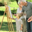 Stock Video: Grandparents and grandson painting canvas