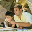 Father and son looking at a map near a tent — Stock Video