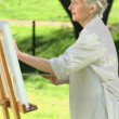 Stock Video: Elderly female painting canvas