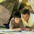 Dad and son looking at a map in front of a tent — Stock Video