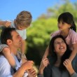 Children laughing on the shoulders of parents — Vídeo Stock