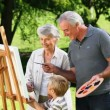 Stock Video: Young boy and grandparents painting canvas