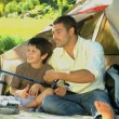 Father teaching the use of the fishing rod to his son sitting in front of a tent — Vídeo de stock