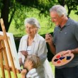 Stock Video: Boy and grandparents painting white canvas