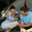 Family looking at a map near a tent — Stock Video