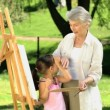 Stock Video: Young child painting canvas with grandmother