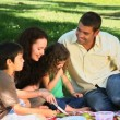 Parents enjoying a picnic with children on a tablecloth — Vídeo Stock