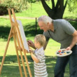 Stock Video: Little boy painting white canvas with grandfather