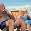 Man listening to music sitting on beach chairs with his wife — Stock Video #22706203