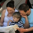 Family looking at a map near a tent — Vídeo Stock
