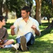 Father talking with his son sitting on the grass — Stock Video #22706413
