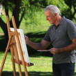 Stock Video: Senior male painting canvas