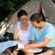 Couple looking at a map near a tent — Stock Video