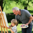 Stock Video: Young boy painting white canvas with grandad