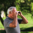 Old man looking through binoculars — Stock Video