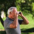 Old man looking through binoculars — Stock Video #22706703
